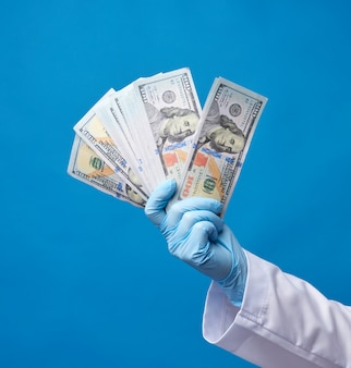 Physician in a white coat, wearing blue sterile gloves, doctor holds a pack of paper money, anti-corruption concept