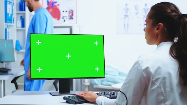 Physician writing diagnose on computer with green screen and assistant wearing blue uniform in the background. medic in white coat working on monitor with chroma key in clinic cabinet to check patient