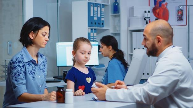 Medico che scrive diagnostica e trattamento negli appunti. operatore sanitario, medico specialista in medicina che fornisce servizi di assistenza sanitaria esame di consultazione nel gabinetto ospedaliero