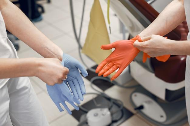 의사는 리셉션을 준비하고 의사는 장갑을 끼고 장갑은 손에 낀다