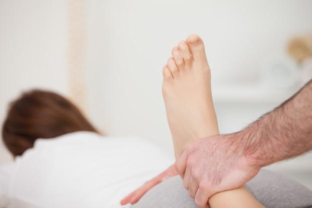 Physioが彼女の足を操作しながら前方に横たわる女性