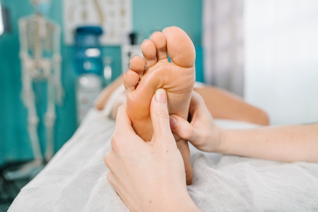 Physiotherapeutic foot massage in a background cyan clinic