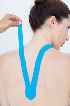 Physiotherapist applying blue kinesio tape to patients back