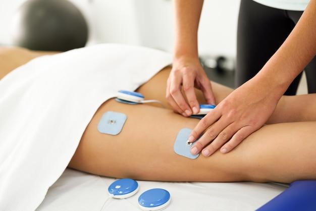 若い女性の足に物理療法で電気刺激を加える理学療法士。