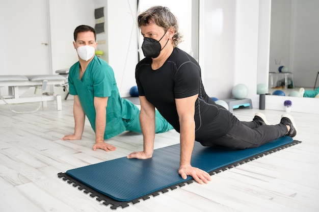 Physiotherapist assisting man in performing exercise on mat.