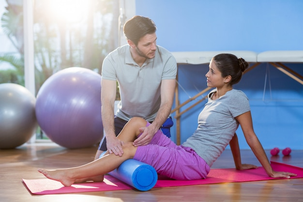Physiotherapist assisting woman while exercising on exercise mat