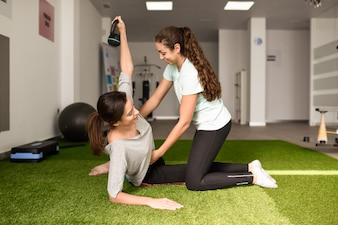 Physiotherapist assisting young caucasian woman with exercise with dumbbell