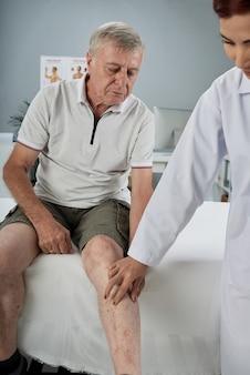 負傷した脚をチェックする理学療法士