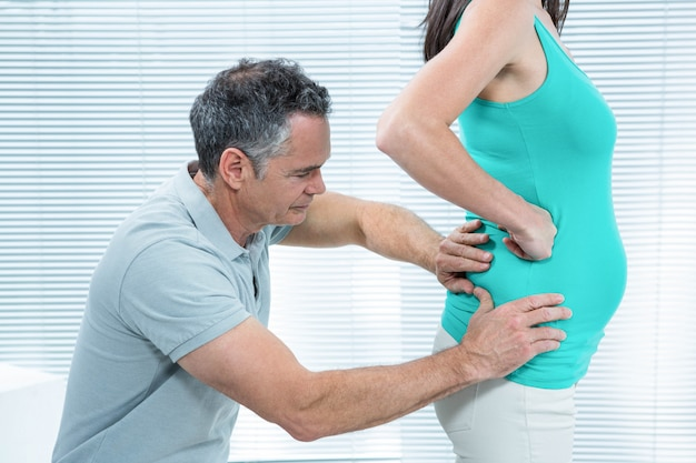 Physiotherapist checking pregnant woman lower back in clinic