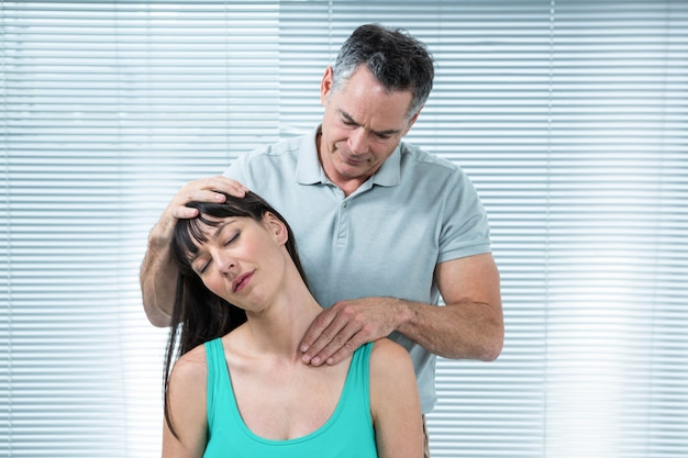 Physiotherapist checking pregnant woman neck in clinic