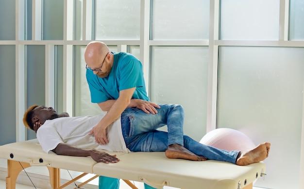 リハビリテーションセンターのスポーツフィジで年配の男性とセラピーセッションを行っている理学療法士...