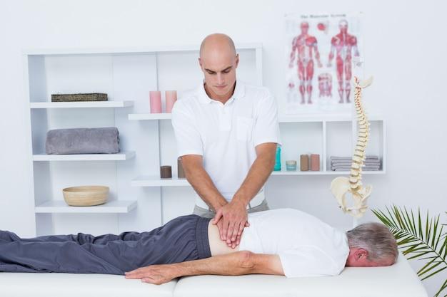 Физиотерапевт делает массаж спины своему пациенту