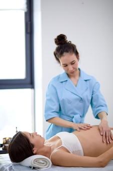 스파 센터에서 아름다운 임산부에게 배 마사지를 하는 물리치료사, 젊은 엄마가 될 젊은 엄마가 파란색 유니폼을 입은 전문가에게 마사지를 받으며 침대에 누워 있습니다. 측면보기. 임산부에 초점