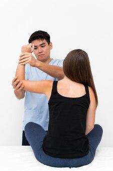 여성 환자와 팔꿈치 운동을하는 물리 치료사
