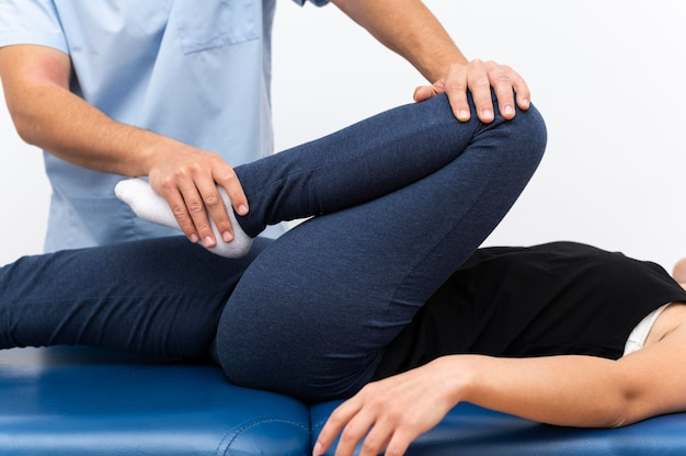 Physiotherapist doing exercises with female patient