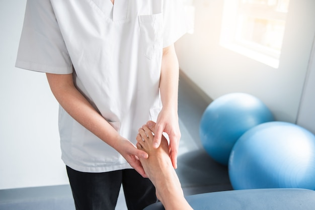 Physiotherapist doing a foot massage of a patient in the clinic. rehabilitation