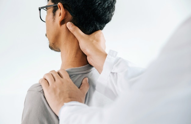 Physiotherapist doing healing treatment on man's neck, chiropractic adjustment