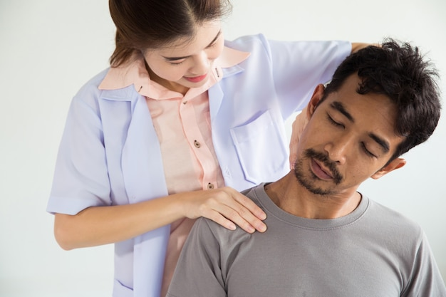 Physiotherapist doing healing treatment on man's neck