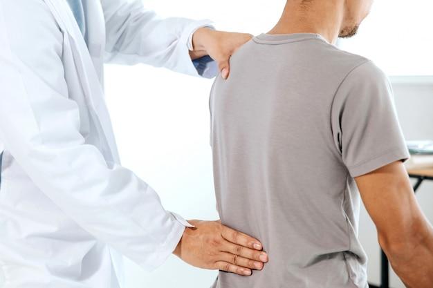물리 치료사는 사람의 등에서 치유 치료를하고 있습니다. 허리 통증 환자, 마사지 치료사
