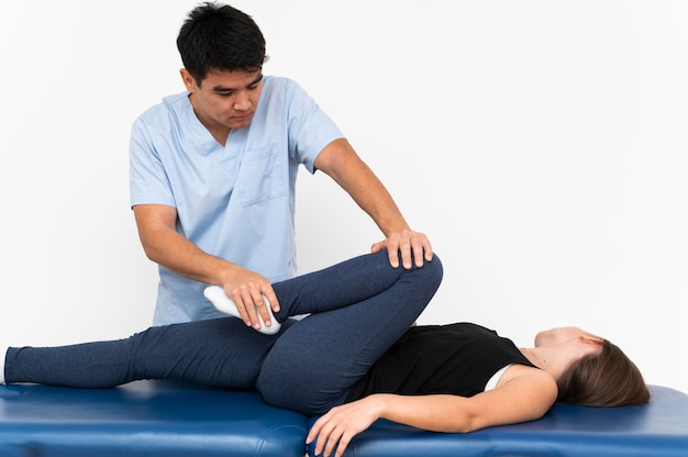 Physiotherapist doing leg exercises with female patient