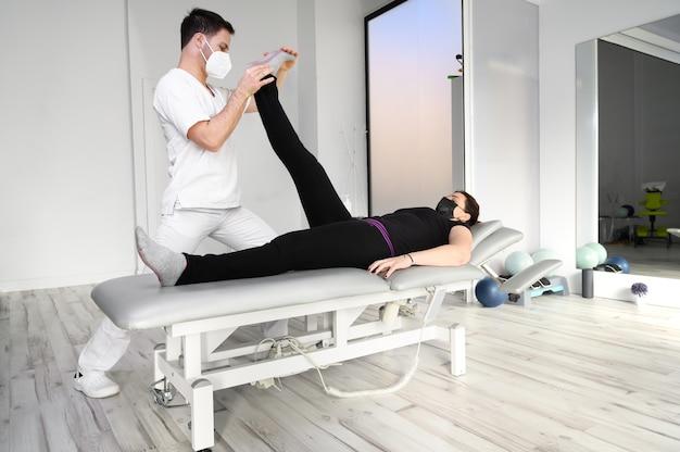 Физиотерапевт делает растяжку мышц ног пациентке. лечение седалищного нерва у женщины