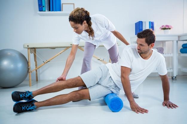 フォームロールを使用して男性に下肢治療を行う理学療法士