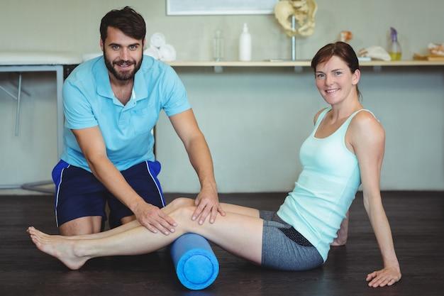 フォームロールを使用して女性に脚の治療を行う理学療法士