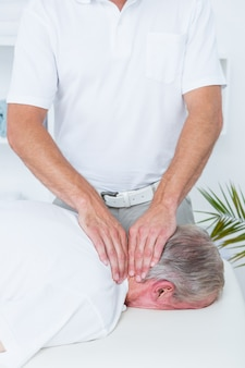 Physiotherapist doing neck massage to his patient