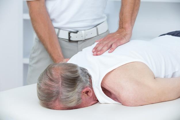 理学療法士が医療事務所の患者に肩のマッサージをしている