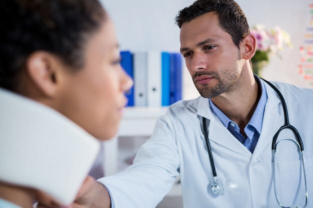 Физиотерапевт осматривает пациентки шеи