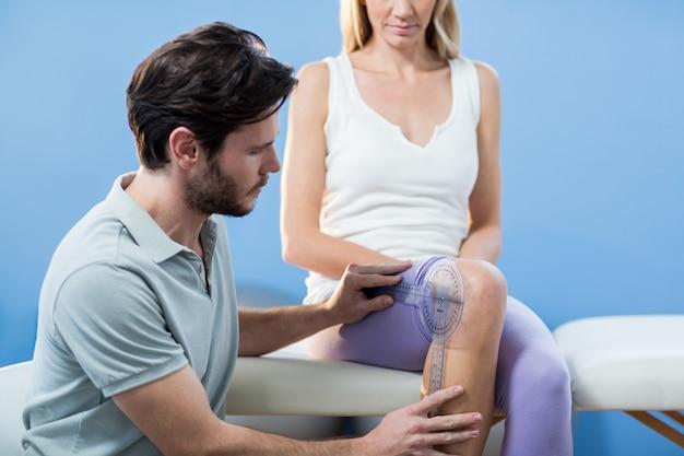 Физиотерапевт осматривает пациентов женского пола с помощью гониометра