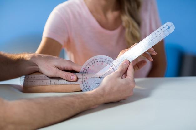 Физиотерапевт осматривает пациентки запястье гониометром