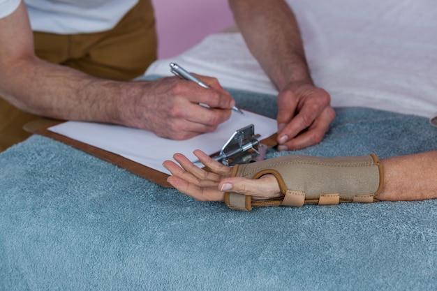 理学療法士が女性患者の手を調べる
