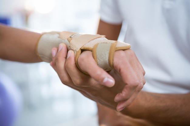 물리 요법가 여성 환자의 손을 검사