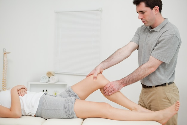 Physiotherapist examining the knee of his patient while touching it