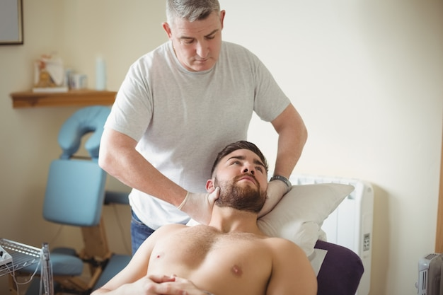 患者の首を調べる理学療法士