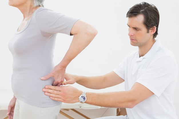 Physiotherapist examining senior womans back Premium Photo