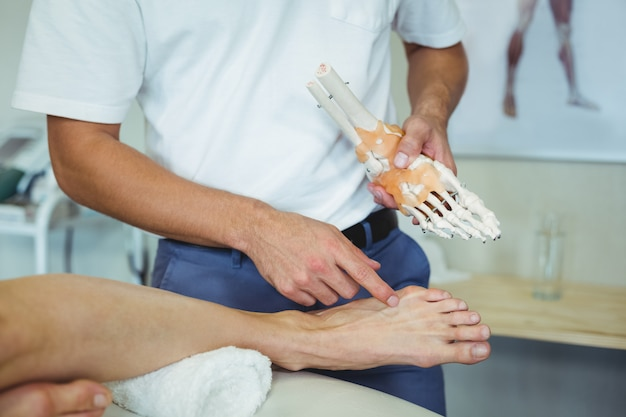 Physiotherapist explaining feet model to patient