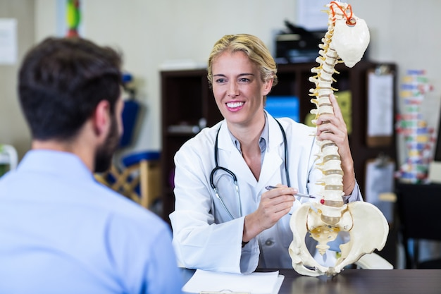 Physiotherapist explaining spine model to patient