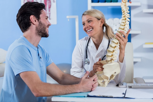 Physiotherapist explaining the spine model to patient