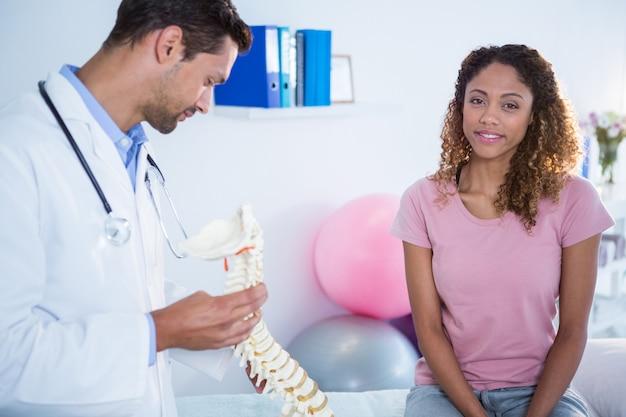 Физиотерапевт, объясняя пациенту модель позвоночника