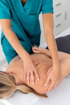 Физиотерапевт делает массаж своему пациенту в клинике