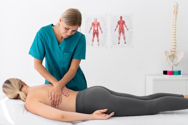 Физиотерапевт делает массаж своему пациенту