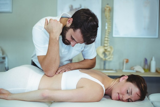 Physiotherapist giving back massage to a woman