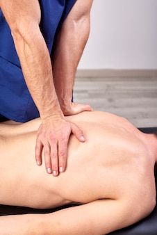 Physiotherapist giving a back massage.