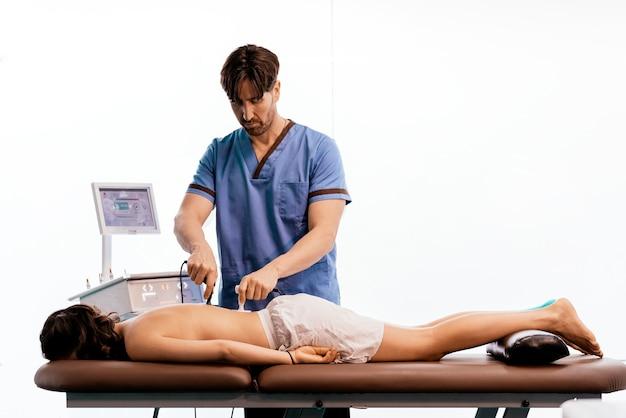 Физиотерапевт дает терапию на спине женщине в клинике. концепция физического лечения