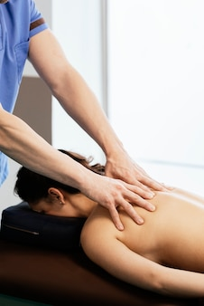 Physiotherapist giving backstroke therapy to a woman in clinic. physical treatment concept
