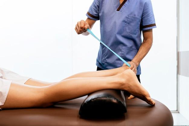 클리닉에서 여성에게 종아리 치료를 제공하는 물리 치료사. 물리 치료 개념