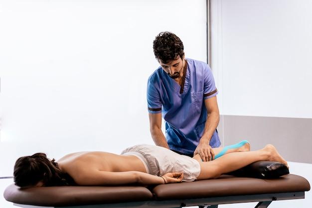 Физиотерапевт дает терапию теленка женщине в клинике. концепция физического лечения