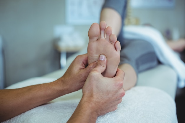 Physiotherapist giving foot massage to a woman